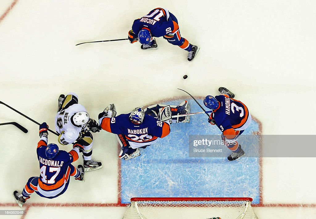 Evgeni Nabokov #20 of the New York Islanders kicks out a shot as James Neal #18 of the Pittsburgh Penguins looks for a rebound at Nassau Veterans Memorial Coliseum on March 22, 2013 in Uniondale, New York. The Penguins defeated the Islanders 4-2.