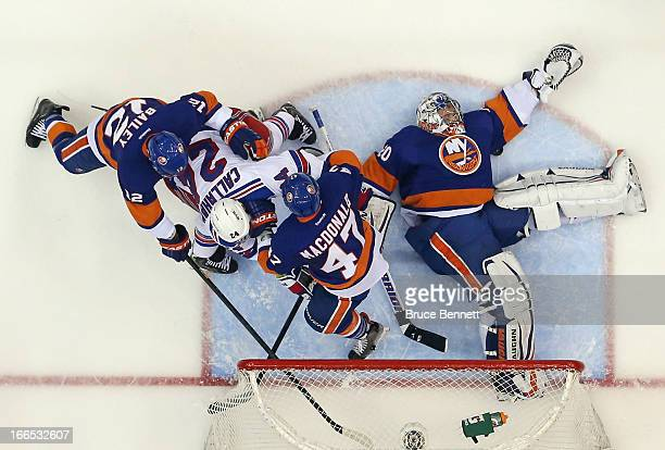 Evgeni Nabokov of the New York Islanders smothers the puck under his arm as the New York Rangers press during the second period at the Nassau...