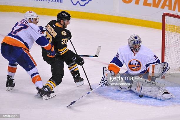 Evgeni Nabokov of the New York Islanders stops the puck against Patrice Bergeron of the Boston Bruins at the TD Garden on December 31, 2013 in...
