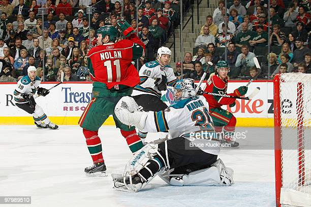 Evgeni Nabokov of the San Jose Sharks makes a glove save while being screened by Owen Nolan of the Minnesota Wild during the game at the Xcel Energy...