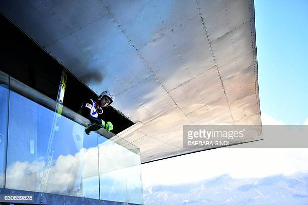 Evgeniy Klimov of Russian Federation looks out as he prepares during a training session of the Four Hills competition of the FIS Ski Jumping World...