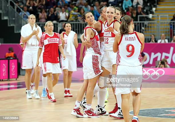 Evgeniya Belyakova and Irina Osipova of Russia celebrate with Becky Hammon after defeating Brazil in the Women's Basketball Preliminary Round match...