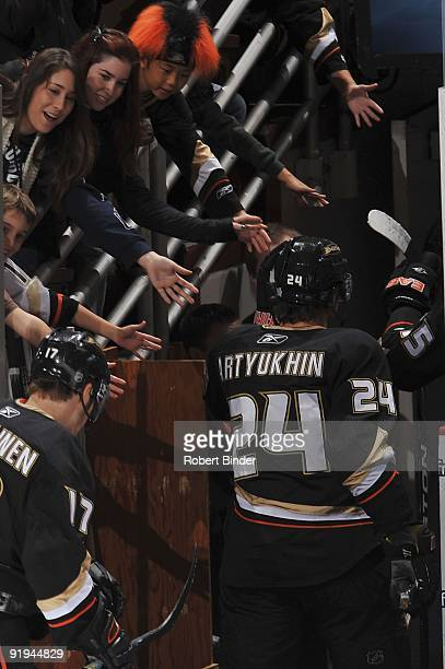 Evgeny Artyukhin of the Anaheim Ducks high fives fans as he heads to the locker room after pre game warm ups prior to the game against the Minnesota...
