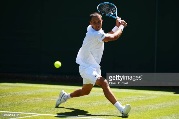 Evgeny Donskoy of Russia returns to Philipp Kohlschreiber of Germany during their Men's Singles first round match on day one of the Wimbledon Lawn...