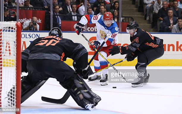 Evgeny Kuznetsov of Team Russia stickhandles the puck in on Matt Murray with pressure from Morgan Rielly of Team North America during the World Cup...