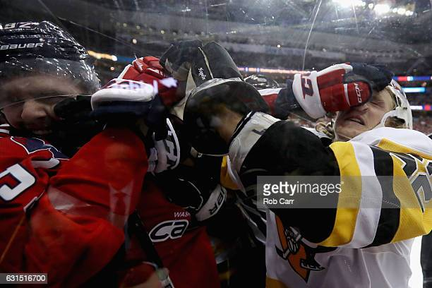 Evgeny Kuznetsov of the Washington Capitals and Carl Hagelin of the Pittsburgh Penguins fight in the third period at Verizon Center on January 11...