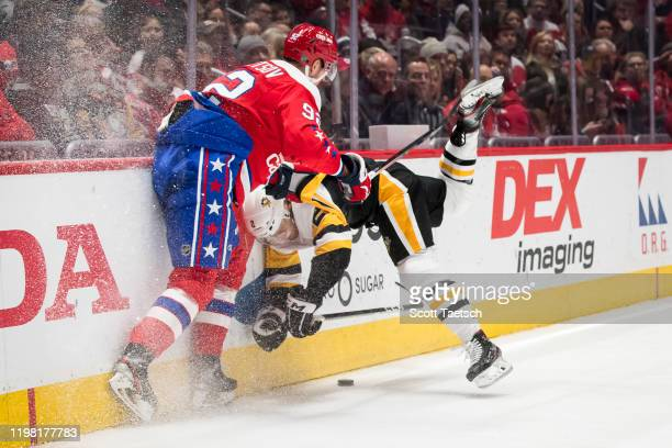 Evgeny Kuznetsov of the Washington Capitals checks Chad Ruhwedel of the Pittsburgh Penguins during the second period at Capital One Arena on February...