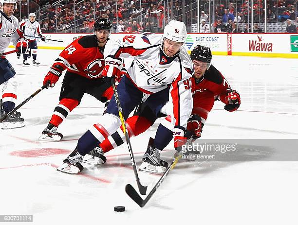 Evgeny Kuznetsov of the Washington Capitals moves the puck around Jon Merrill of the New Jersey Devils during the third period at the Prudential...