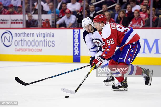 Evgeny Kuznetsov of the Washington Capitals skates with the puck against Alexander Burmistrov of the Winnipeg Jets in the second period during a NHL...