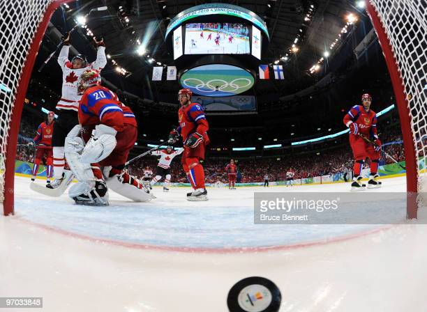 Evgeny Nabokov of Russia gives up a goal against Corey Perry of Canada in the first period during the ice hockey men's quarter final game between...