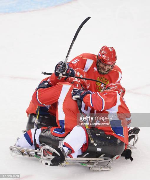 Evgeny Petrov of Russia celebrates with team mates after scoring his team's second goal during the Ice Sledge Hockey Preliminary Round Group A match...
