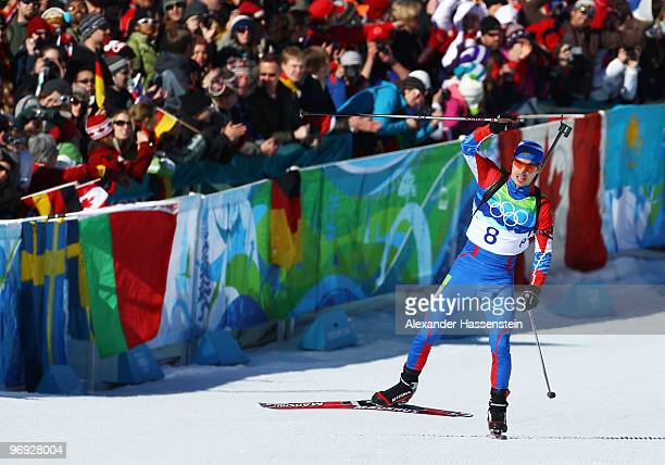 Evgeny Ustyugov of Russia celebrates before crossing the line to win gold in the men's biathlon 15 km mass start on day 10 of the 2010 Vancouver...
