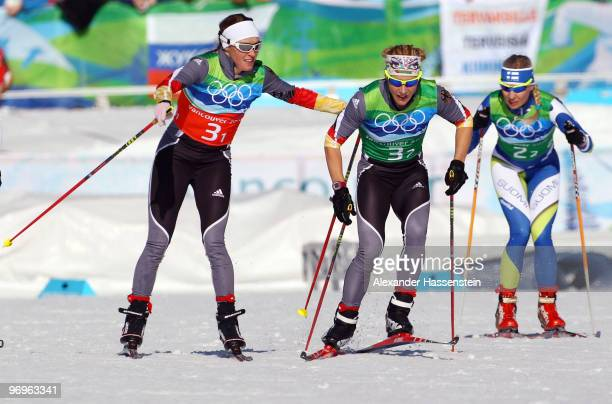 Evi SachenbacherStehle and Claudia Nystad of Germany and Riikka Sarasoja of Finland compete during the cross country skiing ladies team sprint final...