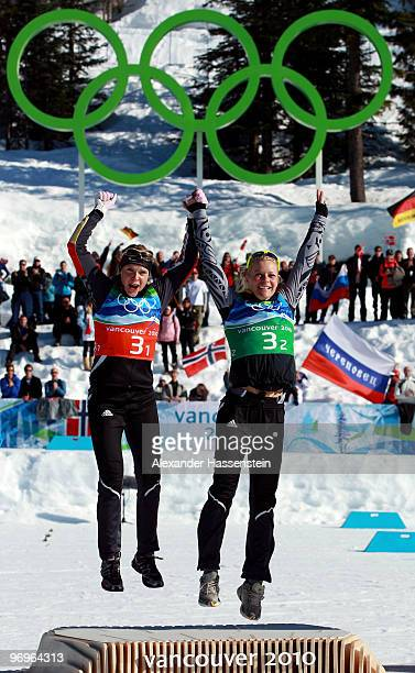 Evi SachenbacherStehle and Claudia Nystad of Germany celebrate winning the gold medal during the flower ceremony for the women's team sprint...