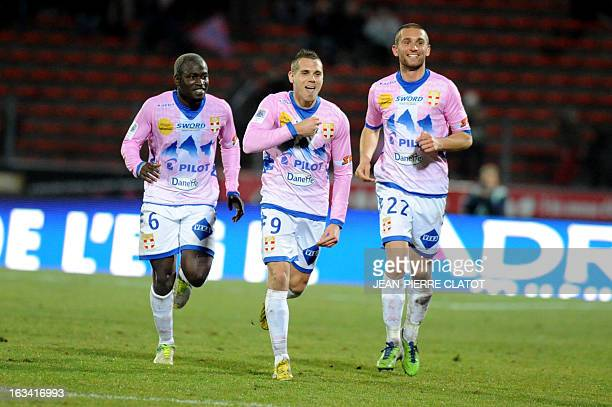 Evian's French forward Kevin Berigaud is congratulated by his teammates after scoring a goal during the French L1 football match Evian vs Sochaux on...