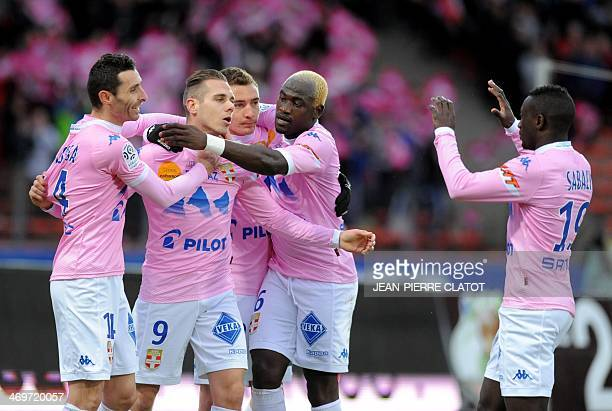 Evian's French forward Kevin Berigaud is congratulated by teammates after scoring during the French L1 football match between Evian and Lille on...