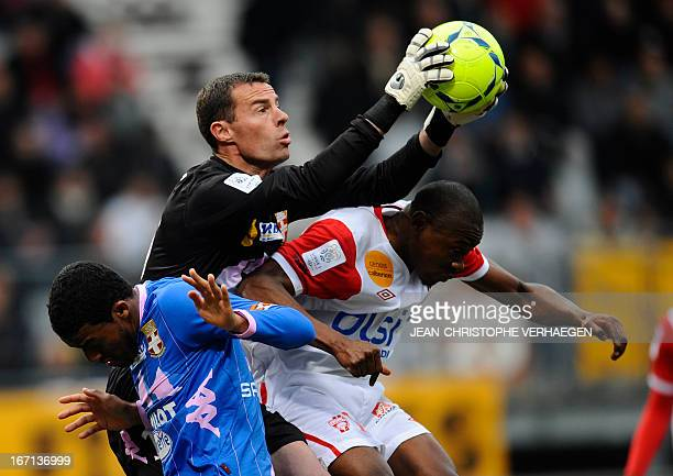 Evian's French goalkeeper Bertrand Laquait catches the ball as Evian's Brazilian defender Betao and Nancy's Cameroonian forward Paul Alo'o Efoulou...