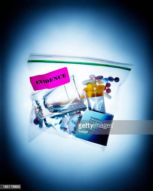 Evidence bag of shot glass and pills