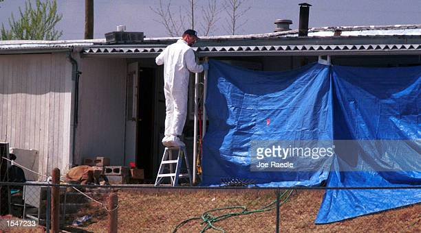 A FBI evidence response personnel member inspects a trailer home where a woman says she was kidnapped and tortured over a threeday period in Elephant...