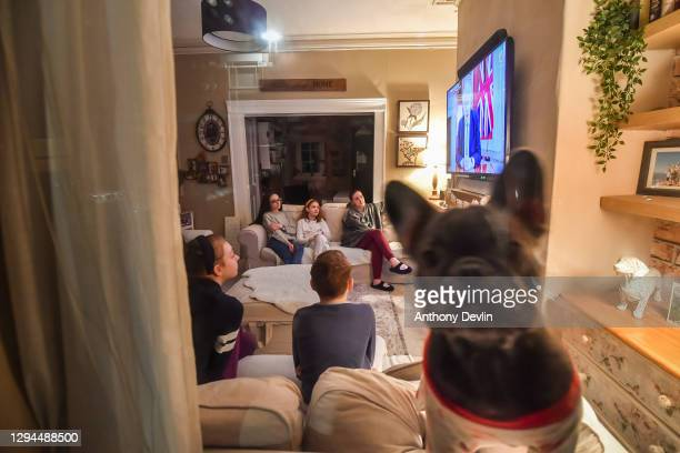 Evie the bulldog looks out of a front window as children Eryn, Ewen, Gwen, Emily and Olivia watch Prime Minister Boris Johnson make a televised...