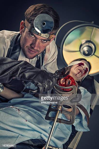 Evil Doctor cutting on missing hand of helpless female victim