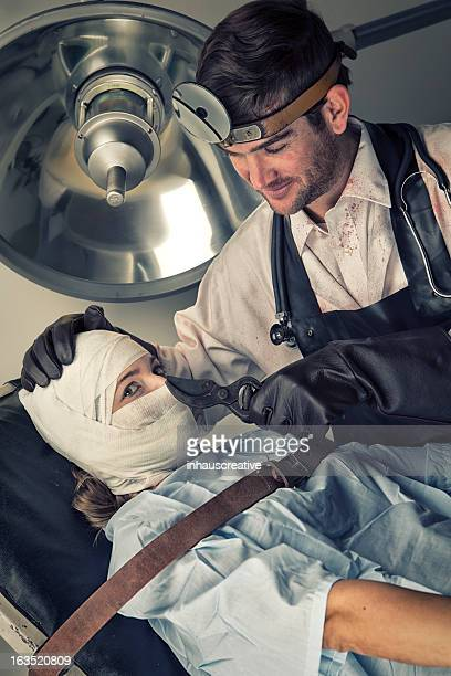 evil doctor teasing before torturing helpless female victim - female torture stock pictures, royalty-free photos & images