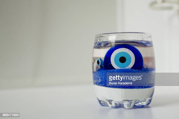 evil eye in cup - lucky charms stock photos and pictures