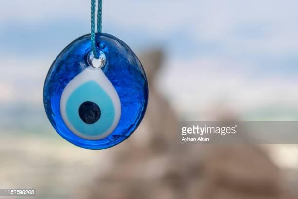 evil eye in wish tree behind uchisar castle in cappadocia, nevsehir, central anatolia of turkey - perlenschnur stock-fotos und bilder