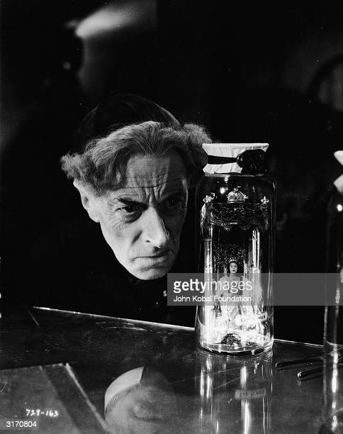 Evil scientist Dr Pretorius peers at a tiny queen imprisoned in a glass jar in a scene from 'Bride of Frankenstein' directed by James Whale The...