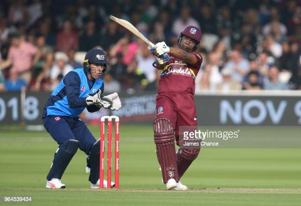 Evin Lewis of West Indies bats as wicketkeeper Luke Ronchi of the ICC World XI looks on during the Hurricane Relief T20 match between the ICC World...
