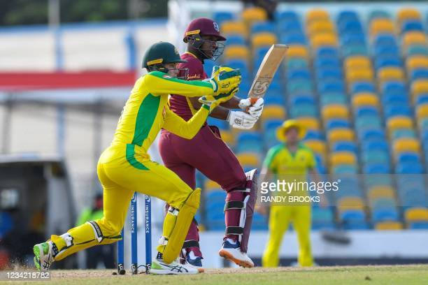 Evin Lewis of West Indies hits 4 as Alex Carey of Australia attempts to catch during the 3rd and final ODI between West Indies and Australia at...