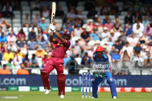 Evin Lewis of West Indies plays to the offside as Afghanistan wicketkeeper Ikram Ali Khil looks on during the Group Stage match of the ICC Cricket...