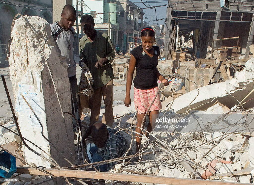 Evoiel Cormeille (bottom) searches for his wife's passport with a valid US visa kept in a suitcase buried in the rubble of her beauty salon as his son Philippe (L), 17, and his 15-year-old daughter Odette (R) and a passerby watch in downtown Port-au-Prince on January 18, 2010, six days after an earthquake measuring 7.0 on the open-ended Richter scale hit the Haitian capital. Cormeille hopes that with his wife and the rest of the family could join relatives living in Florida. AFP PHOTO/Nicholas KAMM