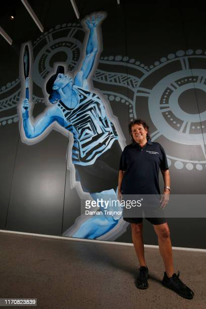 Evonne Goolagong Cawley stands in front of a mural of Ash Barty painted by a group of local artists including David Collins and Indigenous artists...