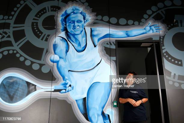 Evonne Goolagong Cawley stands in front of a mural of her painted by a group of local artists including David Collins and Indigenous artists Shaun...