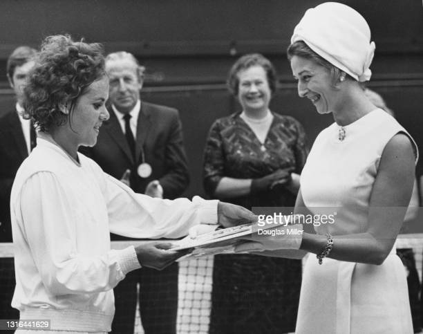 Evonne Goolagong of Australia is presented with the Venus Rosewater Plate by Princess Alexandra after defeating compatriot Margaret Court in their...