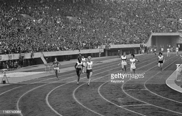 Ewa Klobukowska of the Poland team breaks the tape ahead of Edith McGuire of the United States and Dorothy Hyman of the Great Britain team to win the...