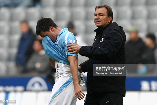 Ewald Lienen head coach of Muenchen comforts his player Antonio Rukavina after the Second Bundesliga match between 1860 Muenchen and 1 FC...