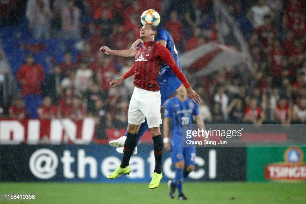 Ewerton of Urawa Red Diamonds and Dave Bulthuis of Ulsan Hyundai compete for the ball during the AFC Champions League round of 16 second leg match...