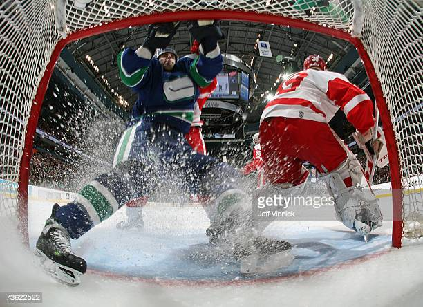 ex Burrows of the Vancouver Canucks runs into the net behind goaltender Dominik Hasek of the Detroit Red Wings during their NHL game at General...