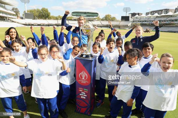 Ex England Cricketer Isha Guha with England International's David Willey and Heather Knight pose with kids and the World Cup during the Cricket World...
