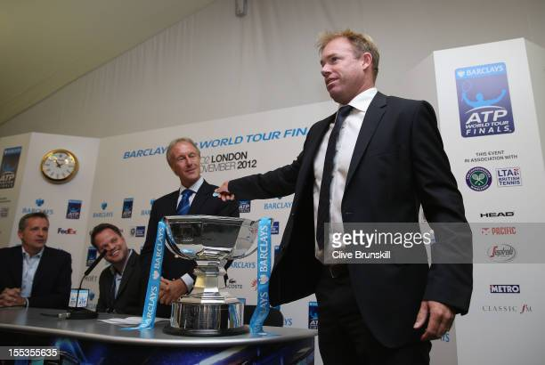Ex Great Britain tennis player Mark Petchey helps with the draw watched by tournament referee Jerry Armstrong at the official tournament draw prior...