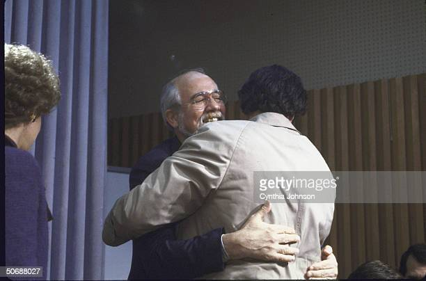 Ex hostages Jeremy Levin and Father Lawrence Martin Jenco hugging as Chairman of No Greater Love Carmella Laspada stands by