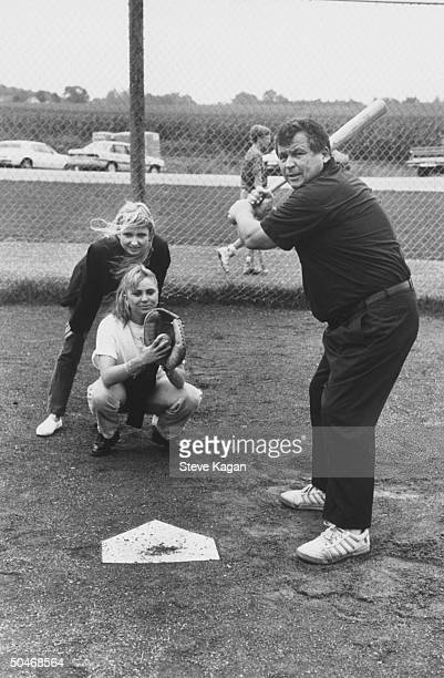 Exactor/selfproclaimed pres cand Tom Laughlin poised w baseball bat at home plate as his daughter Kris plays catcher her sister Teresa backs her up...