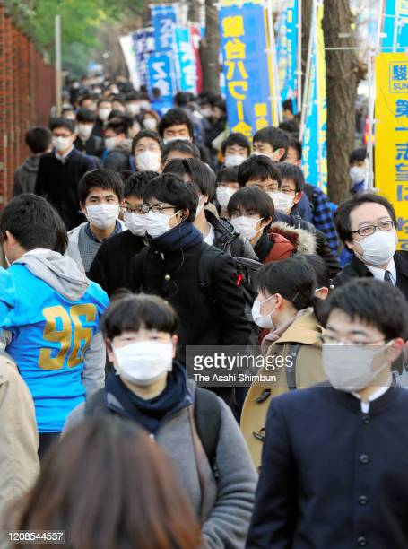Exam takers wearing face masks make their way to the University of Tokyo as the secondary exams of public universities go ahead amid increasing fear...