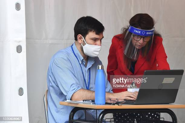 Examiners survey the Baccalaureat examination on June 17, 2020 under a tent set up in the yard at the J. F. Kennedy High School in Rome, as the...