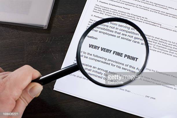 examining the fine print of an employment agreement with a magnifying glass - employment law stock photos and pictures