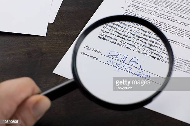 Examining the signature on a rental contract with a magnifying glass