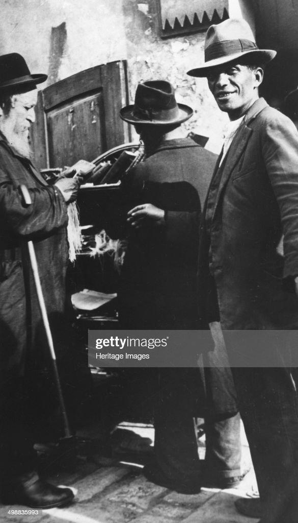 Examining tzitzit, Lemberg Ghetto, USSR, 1941-1944. : News Photo