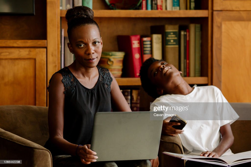 Exasperated Black mother with computer tutoring tired preteen son : Stock Photo